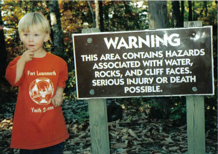 Boy stands beside a danger sign, contemplating risk