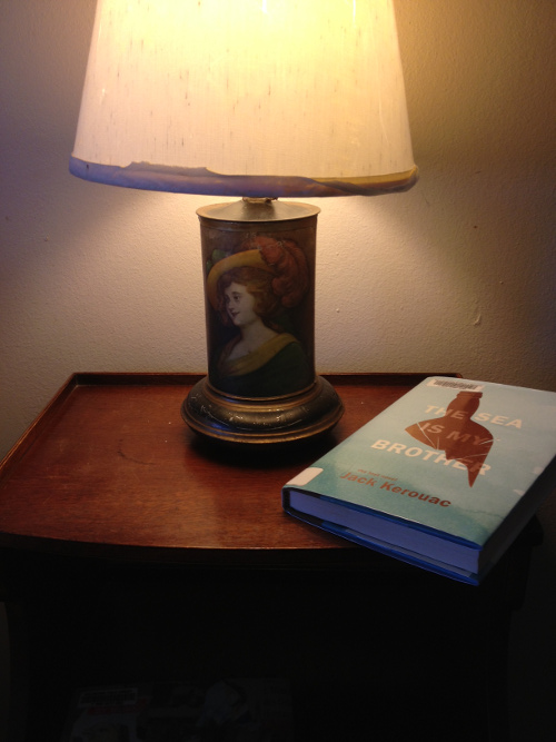 Kerouac's book resting on a nightstand in the dim glow of an antique lamp