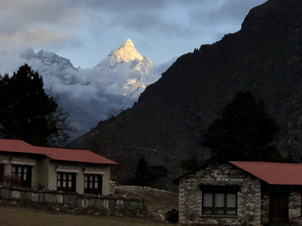 A sharp snowy peak gleams in the first sunlight over a Buddhist monastery